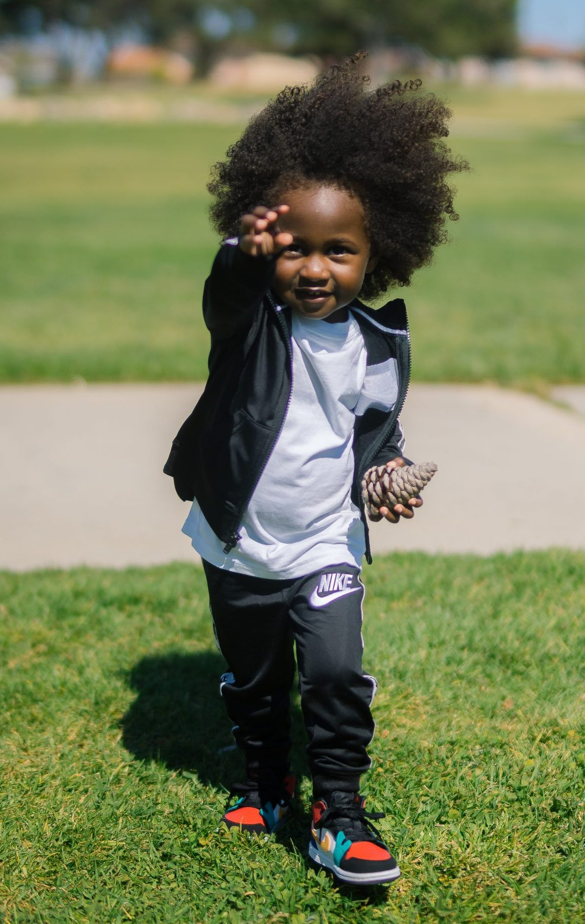 taylor-smith-m6F81ANQzvo-unsplash AA boy in sweatsuit with pinecone